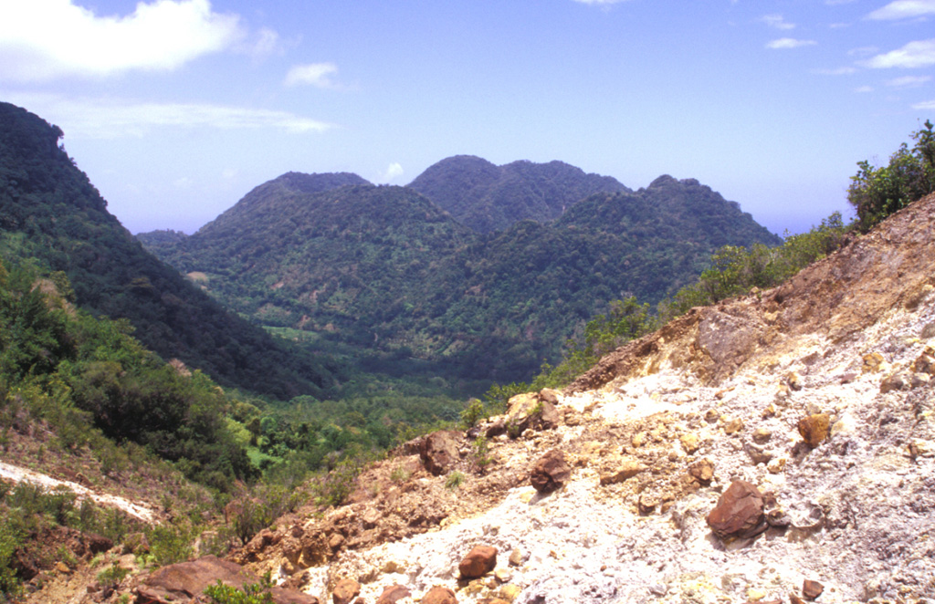 The youngest cluster of lava domes of the Morne Plat Pays volcanic complex, Morne Rouge, Crabier, and Morne Patates (left to right) is seen here from the north at the upper Sulfur Springs thermal area.  The cliff in the shadow at the left is the west-facing wall of the arcuate Morne Plat Pays caldera, which formed about 39,000 years ago in association with the eruption of the Grand Bay Ignimbrite and a lateral flank collapse to the west. Photo by Paul Kimberly, 2002 (Smithsonian Institution).