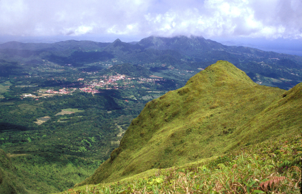 The steep-sided grassy knob in the right foreground is part of the Aileron lava dome, which formed during an eruption about 9700 years ago.  This view looks to the SE towards the town of Morne Rouge (left-center), which was devastated by pyroclastic flows during the 1902 eruption.  The Pleistocene Piton du Carbet volcano lies in the clouds on the right-center horizon. Photo by Lee Siebert, 2002 (Smithsonian Institution).