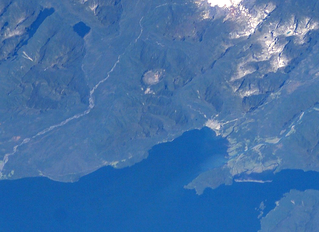 The small circular feature just above the center of this NASA International Space Station image (with north to the upper left) is Chaitén caldera.  It is located 10 km NE of the town of Chaitén, the light-colored area along on the Gulf of Corcovado below and to the right of the caldera.  This small, glacier-free, 3.5-km-wide caldera is of Pleistocene age, but has a rhyolitic Holocene lava dome.   NASA Space Station image ISS006-E-42131, 2003 (http://eol.jsc.nasa.gov/).