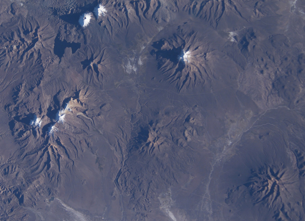 Snow capped volcanoes dot this NASA Space Shuttle image (with north to the upper right) taken along the Chile-Bolivia border.  The snow-capped peak at the far left-center is Guallatiri volcano, and to its right are the three peaks of Nevados Quimsachata, which includes Acotango volcano.  The twin peaks at the upper left are Pomerape and Parinacota, with Laguna Chungara below.  Nevado del Sajama in Bolivia lies at the upper right-center.  At the lower right is the snow-free volcano of Macizo de Larancagua. NASA Space Shuttle image ISS009-E-6848, 2004 (http://eol.jsc.nasa.gov/).