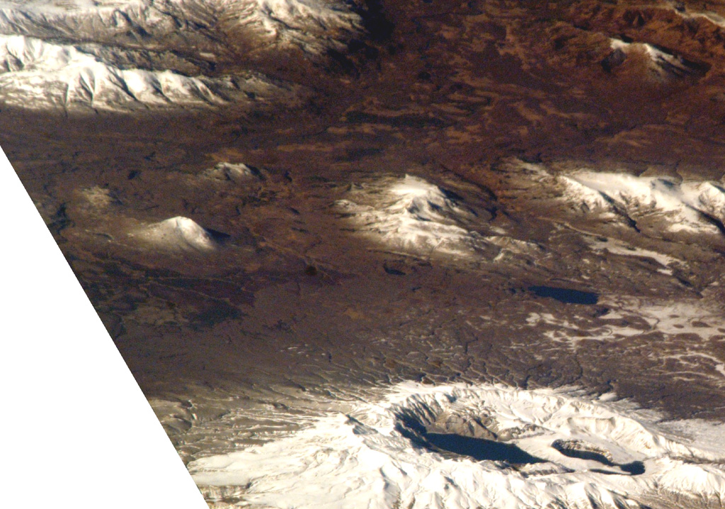 Ksudach is the volcano with multiple crater lakes at the bottom of this NASA Space Shuttle image (with N to the right). The smaller snow-covered cone near the left-center is the 700-m-high Holocene Belenkaya volcano. NASA Space Shuttle image ISS005-E-19216, 2002 (http://eol.jsc.nasa.gov/).