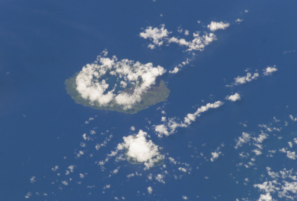 Clouds almost entirely obscure the small island of Kao (lower-center) in this NASA Space Shuttle image, and a circular cloud pattern rises above the caldera rim of the larger island of Tofua (left-center). No historical eruptions are known from Kao, and fresh-appearing lava flows are not seen, although the absence of sufficient time for erosion to produce deep gullies or high sea cliffs suggests a very recent origin. NASA Space Station image ISS008-E-14026, 2004 (http://eol.jsc.nasa.gov/).