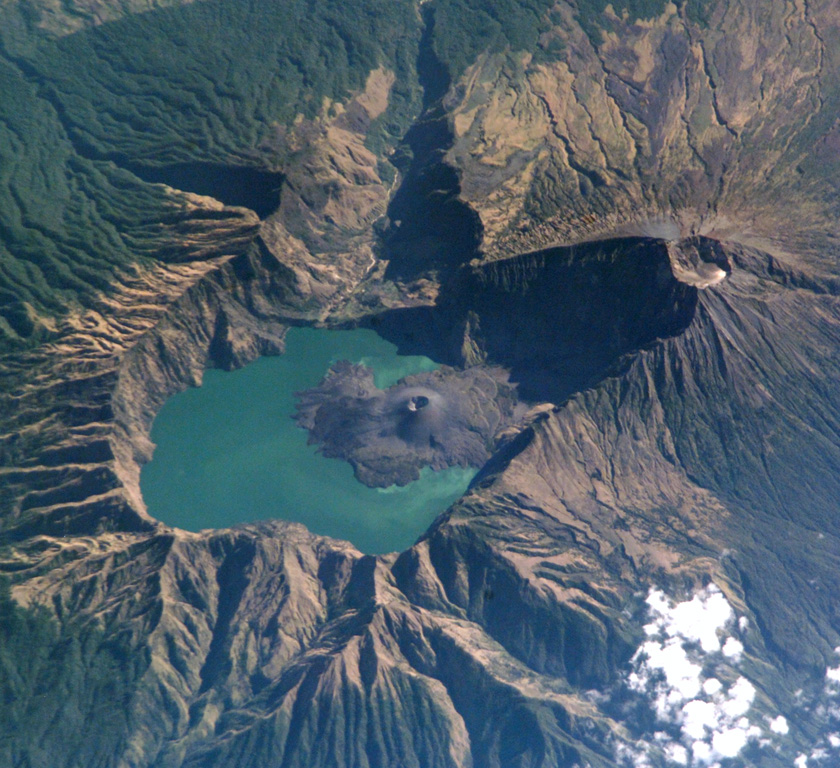 This 2002 NASA Space Shuttle image with N to the top shows the 6 x 8.5 km Segara Anak caldera. The Barujari cone in the center has produced lava flows that have entered the lake. The 3,726-m-high summit of Rinjani (right) contains a crater that postdates caldera formation. NASA Space Shuttle image ISS005-E-15296, 2002 (http://eol.jsc.nasa.gov/).