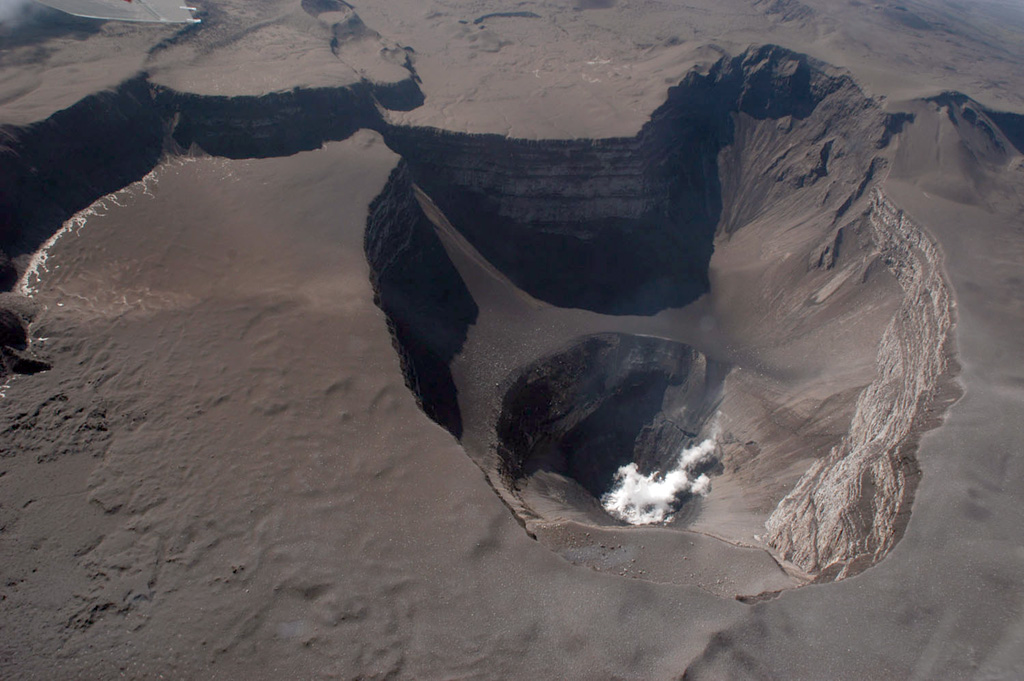 This 19 April 2005 aerial photograph of the Karthala Chahalé crater was taken from the SE. The surface of the lava lake, which had been emplaced the day before, had chilled and was emitting a white plume. Much of the summit area displays recently-deposited tephra from explosive eruptions on the 16th and 17th. Photo by Nicolas Villenueve, 2005 (Université de la Réunion).