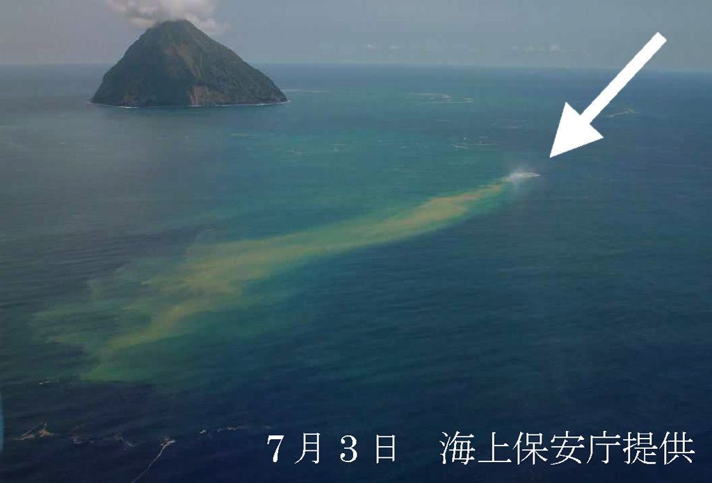 Fukutoku-Okanoba on 3 July 2005 from the NE shows a plume of debris and discoloration extending from the arrow. On the previous day a white plume was observed at Fukutoku-Okanoba, which later was observed to have reached ~1 km above the sea surface. Numerous large and steaming blocks were seen floating on the ocean surface at mid-day on 3 July. The island in the background is Shin-Iwojima. Photo courtesy of Japan Maritime Security and Safety Agency, 2005.