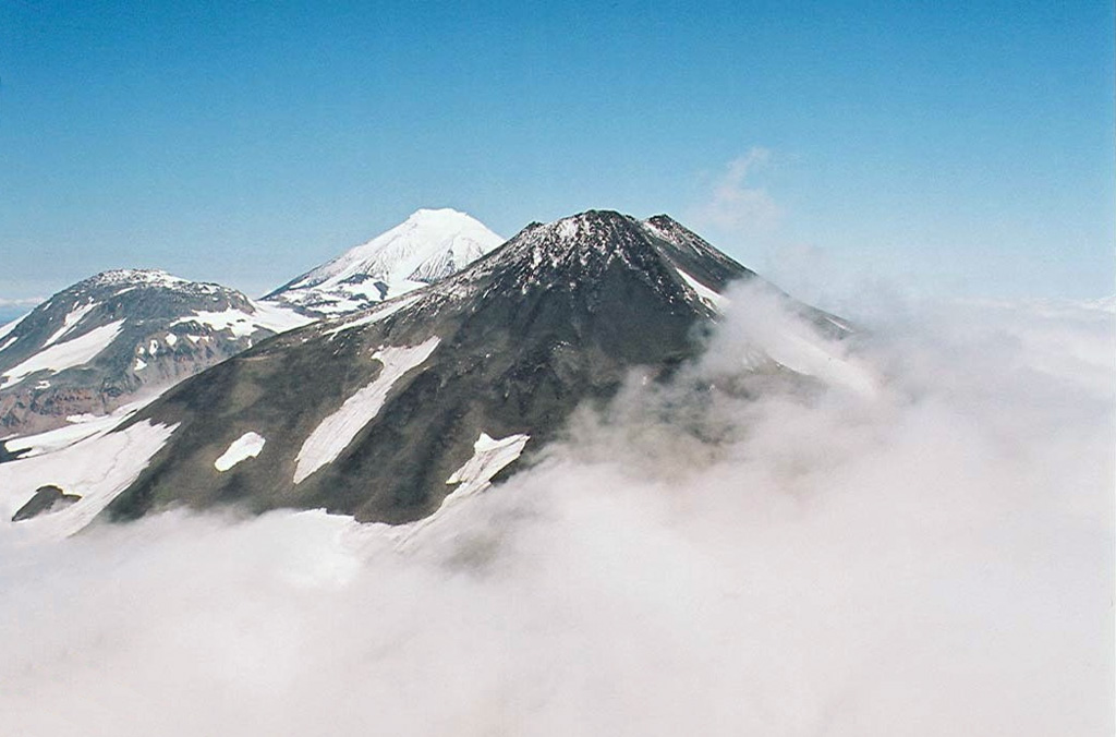 Three volcanoes in the northern Sredinny Range rise above the clouds in this helicopter view from the south. Spokoiny is in the foreground, with snow-covered Ostry in the background. The rounded lower peak on the west (left) flank of Ostry was active during the Holocene. Copyrighted photo by Maria Pevzner, 2005 (Russian Academy of Sciences, Moscow).