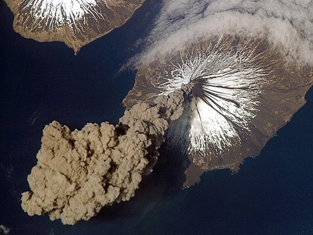 Eruption of Cleveland on 23 May 2006 as photographed from the International Space Station at an orbital altitude of approximately 400 km. The photograph shows the ash plume moving SW from the summit with N at the top and Carlisle Island to the NW.  Courtesy of Jeffrey N. Williams, Flight Engineer and NASA Science Officer, International Space Station Expedition 13 Crew, NASA Earth Observatory.