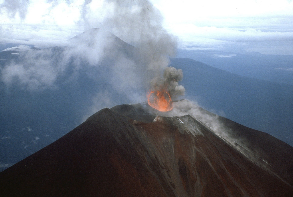 Photograph of Ulawun taken from a helicopter on 25 November 1985. This view from the NE shows the ejection of lava into the air above the vent during Strombolian activity. The other large stratovolcano in the background is Bamus.  Photo by James Mori, Disaster Prevention Research Institute, Kyoto University.