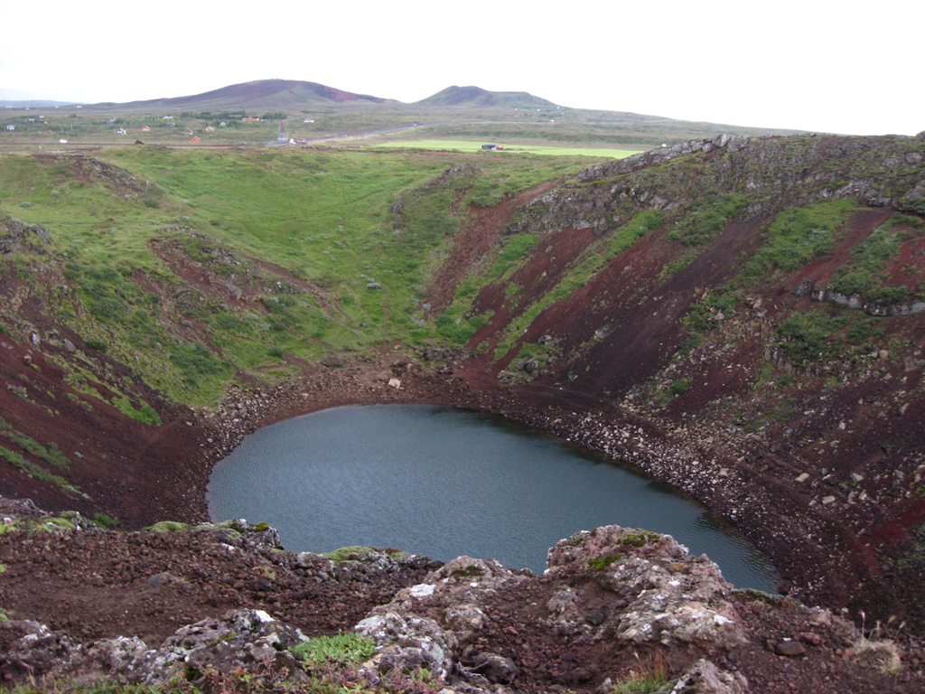 A small pond fills the bottom of the Kerid crater at the northern end of the Tjarnarholar crater row in the Grímsnes volcanic system.  The crater is elliptic in shape, 270 m long, 170 m wide, and 55 m deep.  Other cinder cones of the Holocene Grímsnes volcanic field are visible in the background to the north.  Grímsnes lava flows cover 54 sq km and were erupted from a group of 11 fissures that produced a series of NE-SW-trending crater rows.    Photo by Lee Siebert, 2008 (Smithsonian Institution).