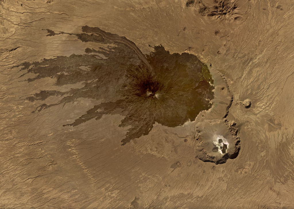 Tarso Toussidé is a nested caldera system in the Tibesti massif in Chad, seen in this November 2019 Planet Labs satellite image monthly mosaic (N is at the top; this image is approximately 44 km across). Trou au Natron is the caldera along the SE boundary, the crater to the NNE is Petit Trou/Doon Kidimi. The long, narrow lava flow to the NW is one of the more recent eruptive products. Satellite image courtesy of Planet Labs, 2019.