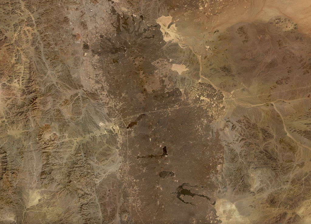 The northern part of the 20,000 km2 Harrat Rahat volcanic field, the largest in Saudia Arabia at 50-75 km wide and ~300 km long, is shown in this November 2019 Planet Labs satellite image monthly mosaic (N is at the top; this image is approximately 192 km across). Earlier work identified 986 vents across the field. Recent lava flows in the northern end encroach on the city of Al-Madinah. Satellite image courtesy of Planet Labs, 2019.